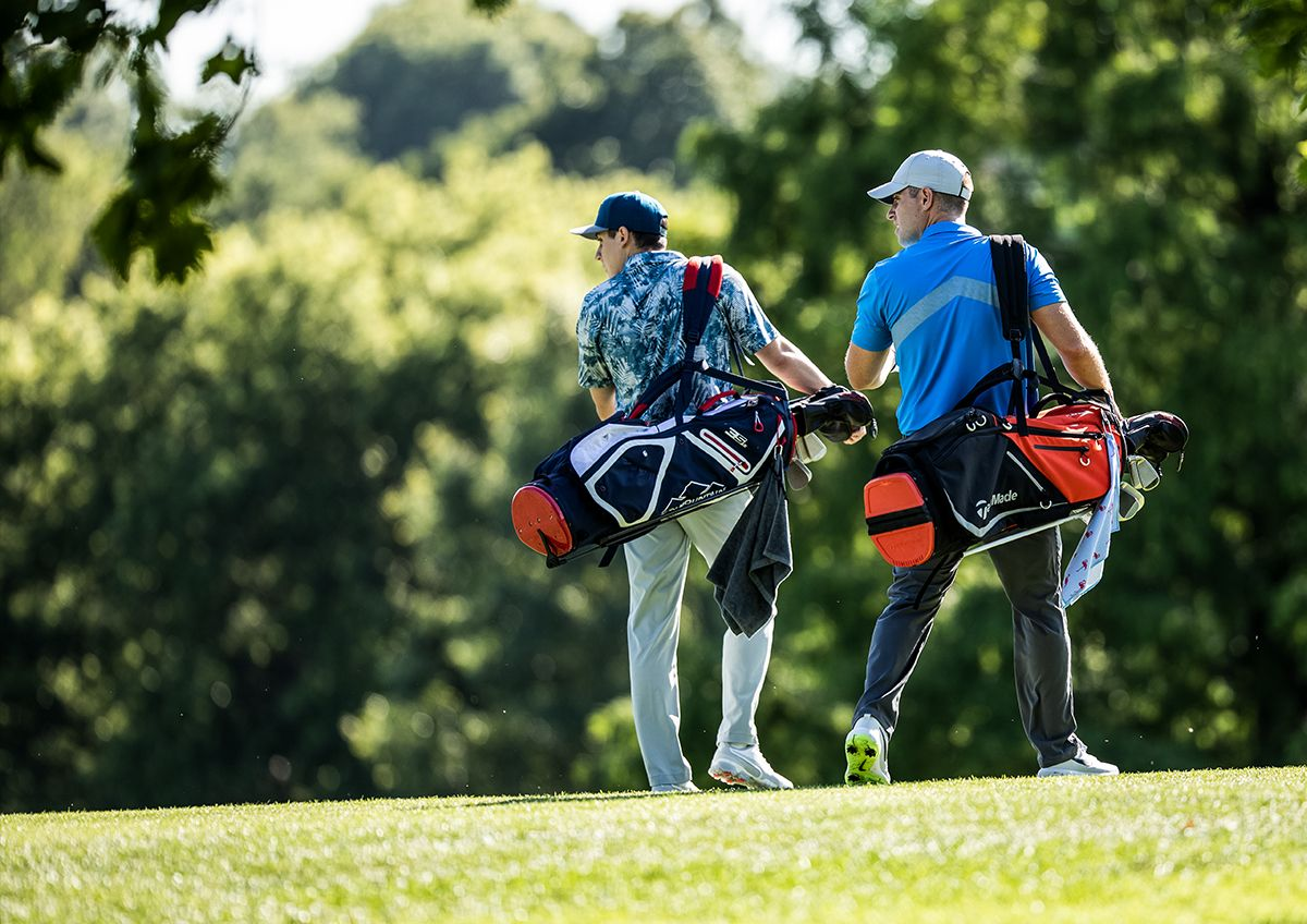Two Golfers Carry Their Clubs On A Golf Course Between Shots