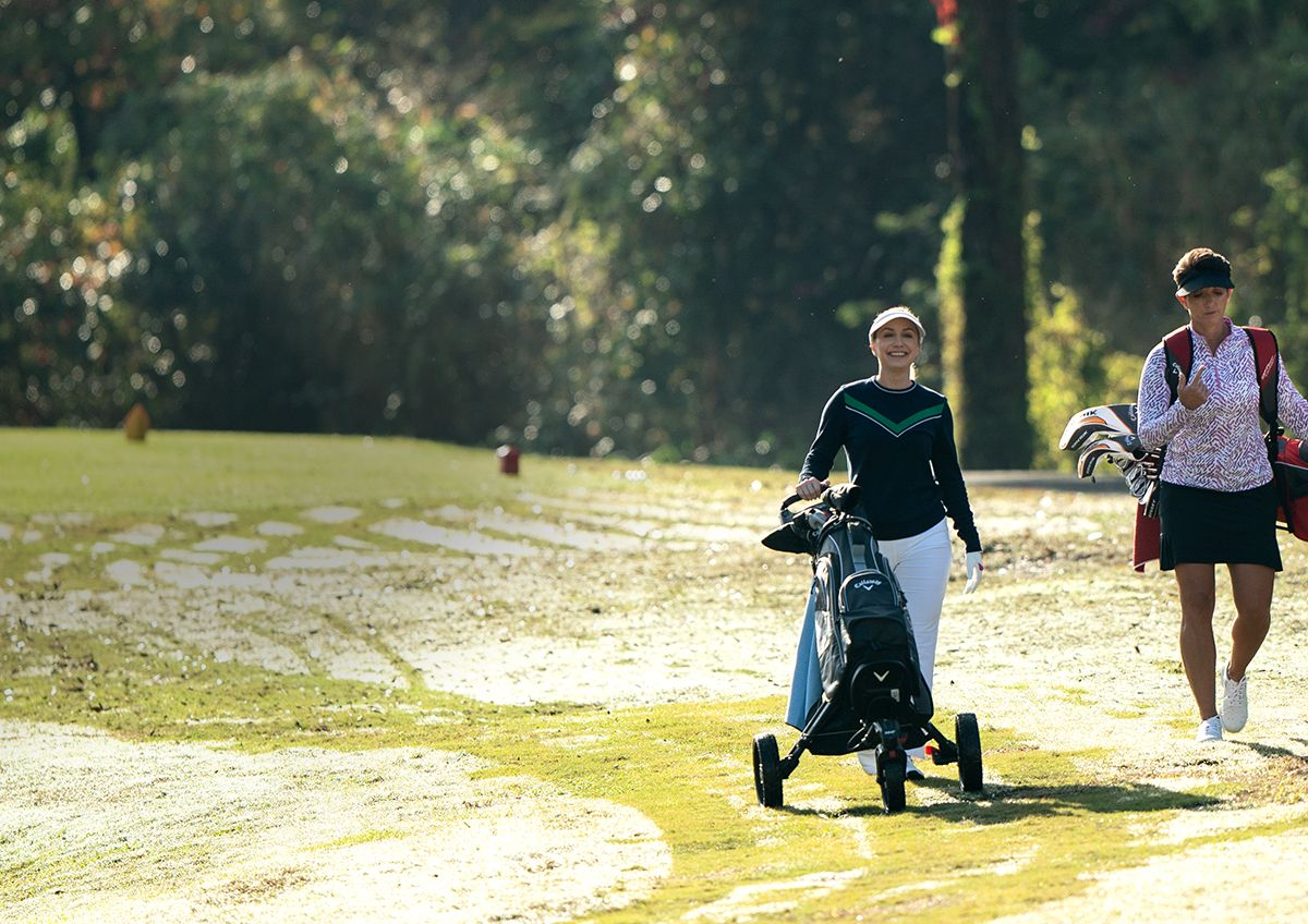 Two Female Golfers Walking The Golf Course