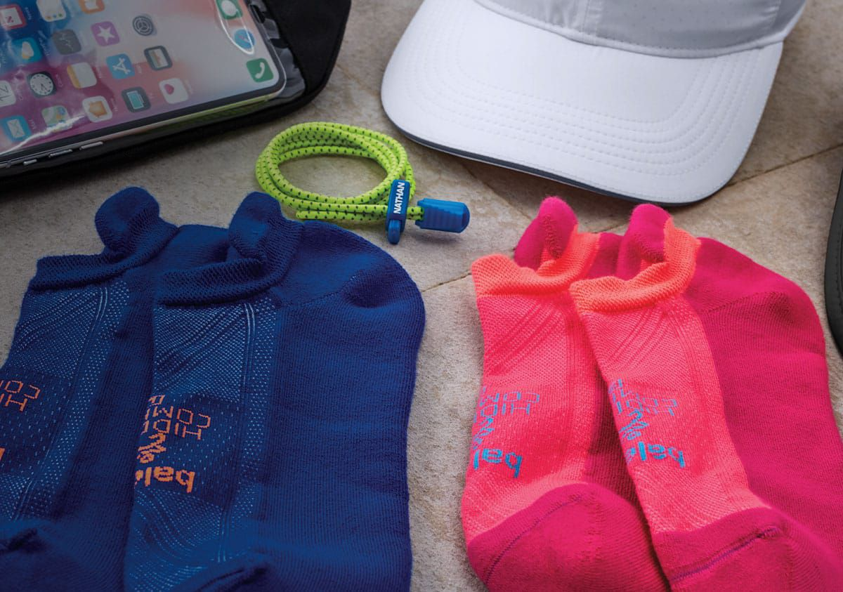 A laydown of running accessories including a hat and socks.
