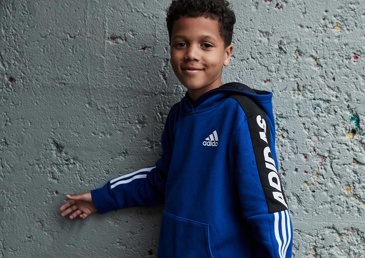 A young boy next to a wall wearing an adidas fleece hoodie.