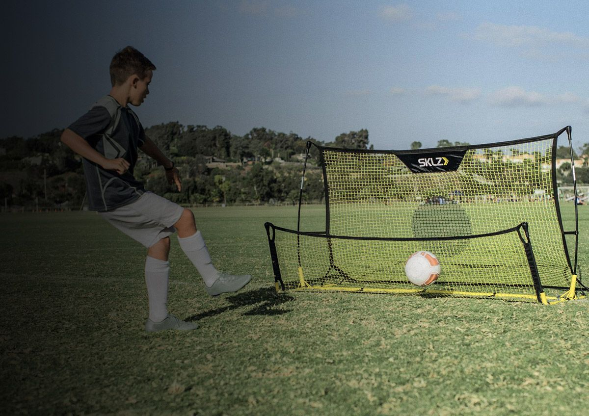 A soccer player uses a soccer training net to practice kicking drills.
