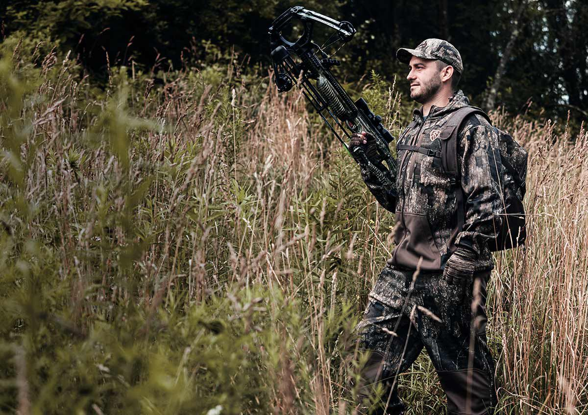 Hunter in full camo and pack walking through tall grass with crossbow in hand