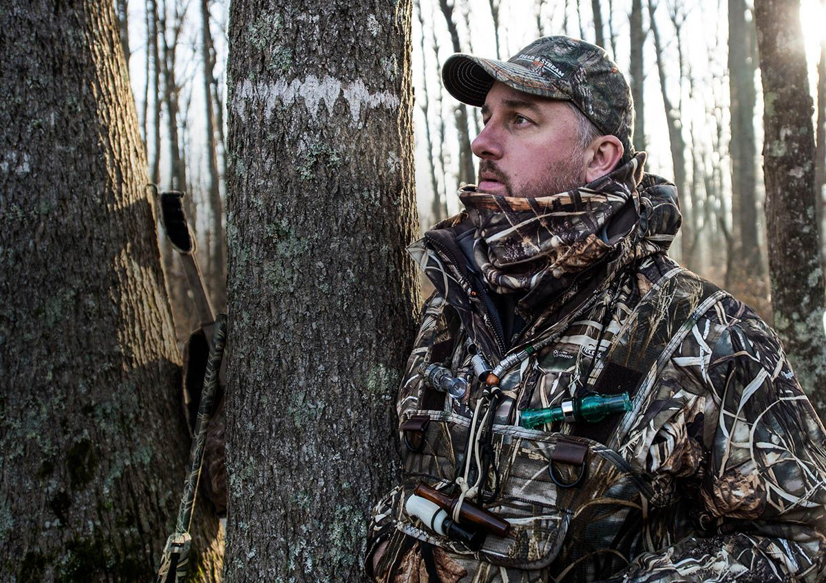 Image of a hunter in the woods looking off into the distance, wearing a Field & Stream camouflage jacket, coveralls and hat.