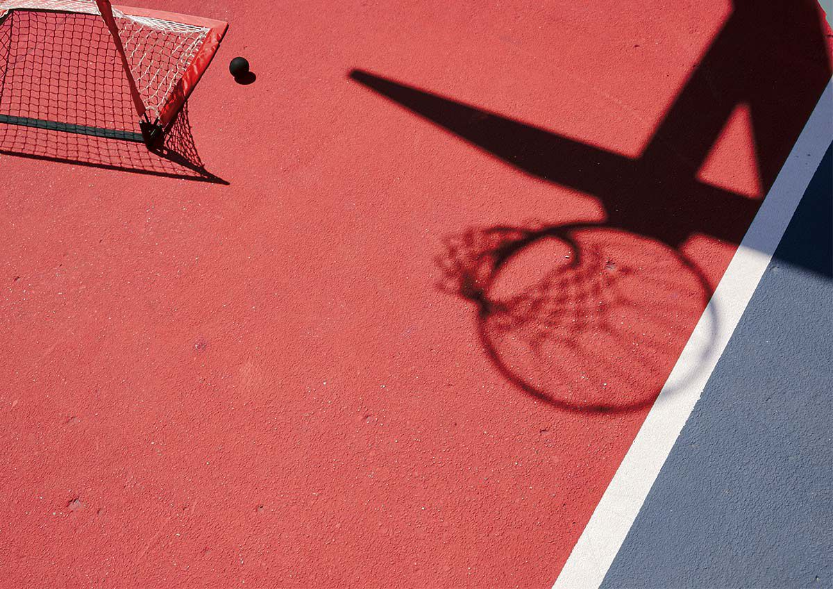 Red court with a hockey net and basketball shadow