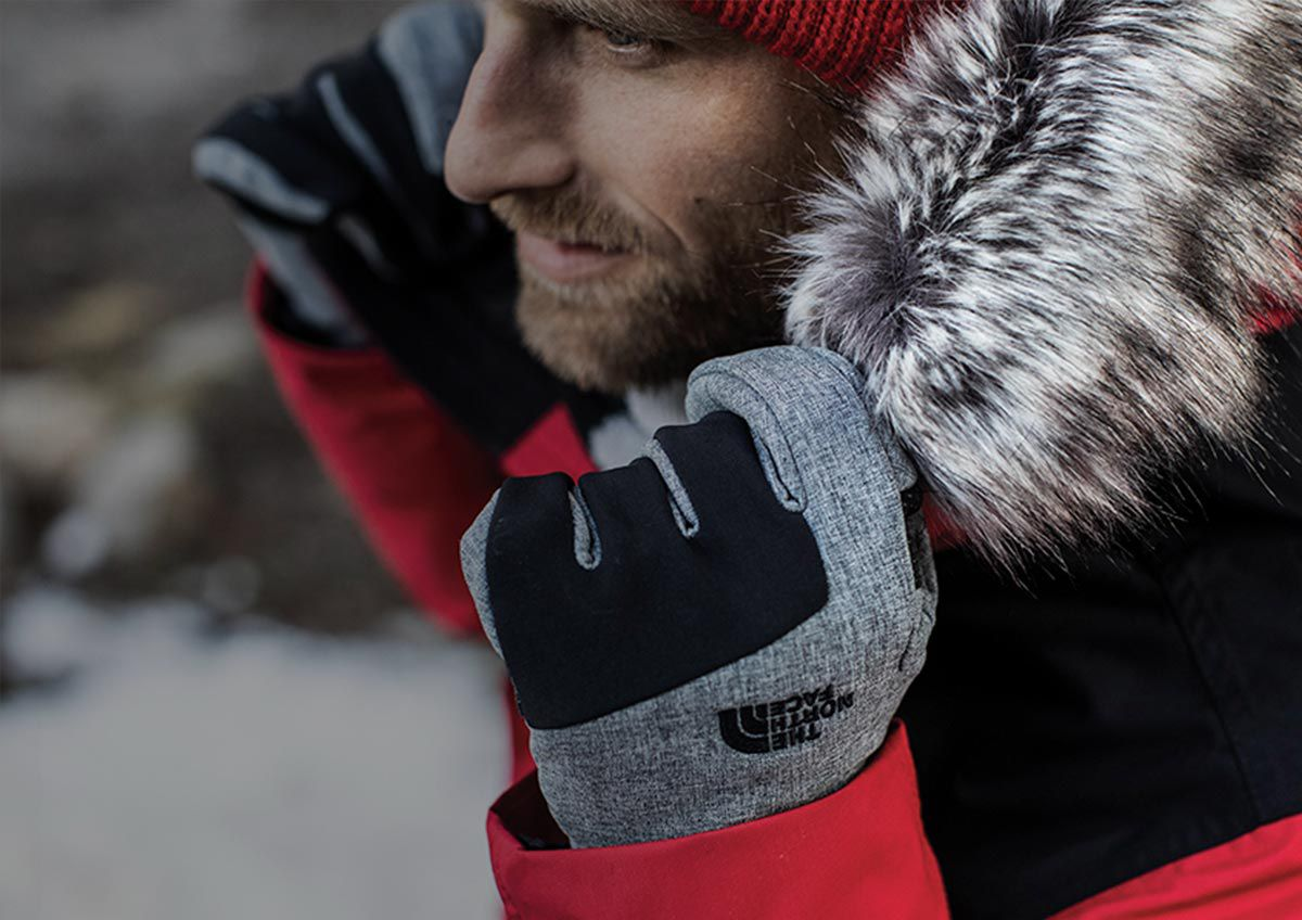 A man pulls his The North Face McMurdo Down Parka III closed while wearing his The North Face Apex ETIP Gloves.