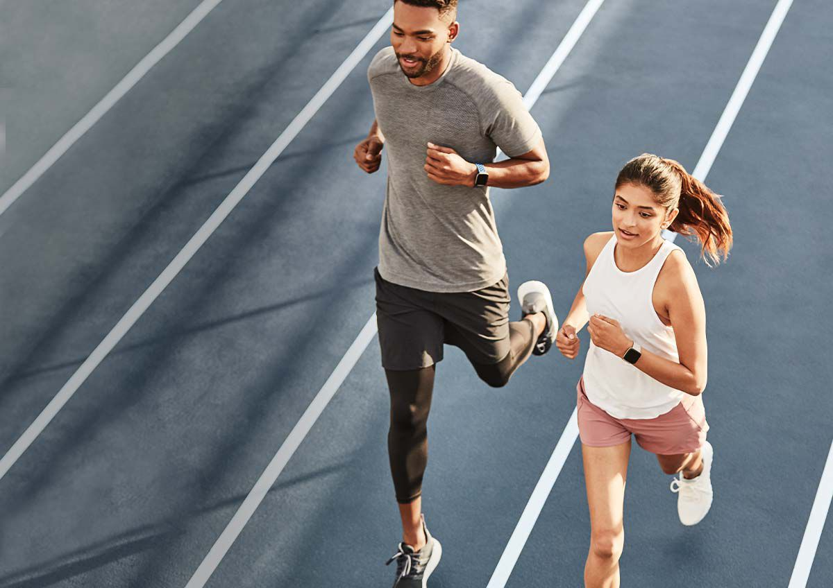 A man and a woman jog on a track while wearing Fitbit activity trackers.