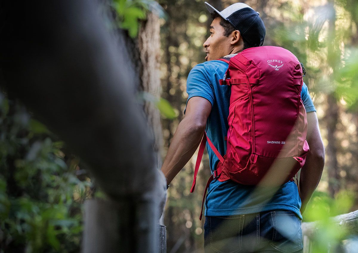 A man on a hike through the woods, looking up over his left shoulder while wearing an Osprey 10001885 22 backpack.