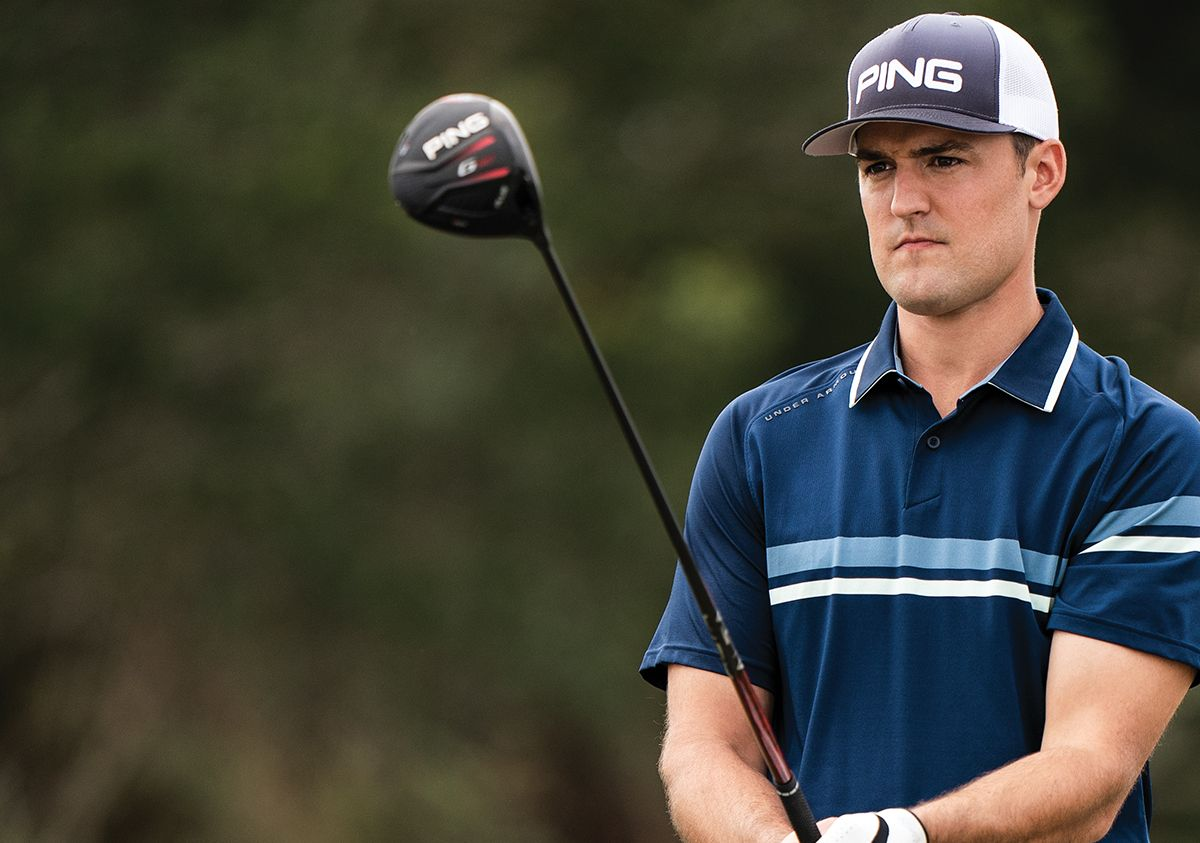 Male Golfer Holding PING G410 Driver And Wearing PING Golf Hat And Blue Striped Golf Polo