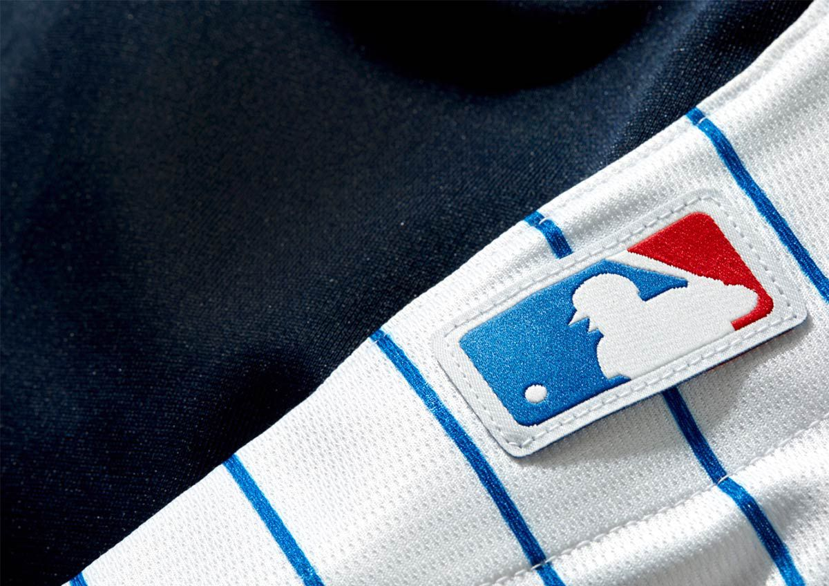 A close up of the MLB logo on a baseball jersey.