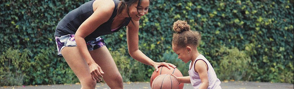Woman bends at the waist near a child, both of them dribbling basketballs. They are backed by what appears to be an ivy wall and are standing on a blacktop.