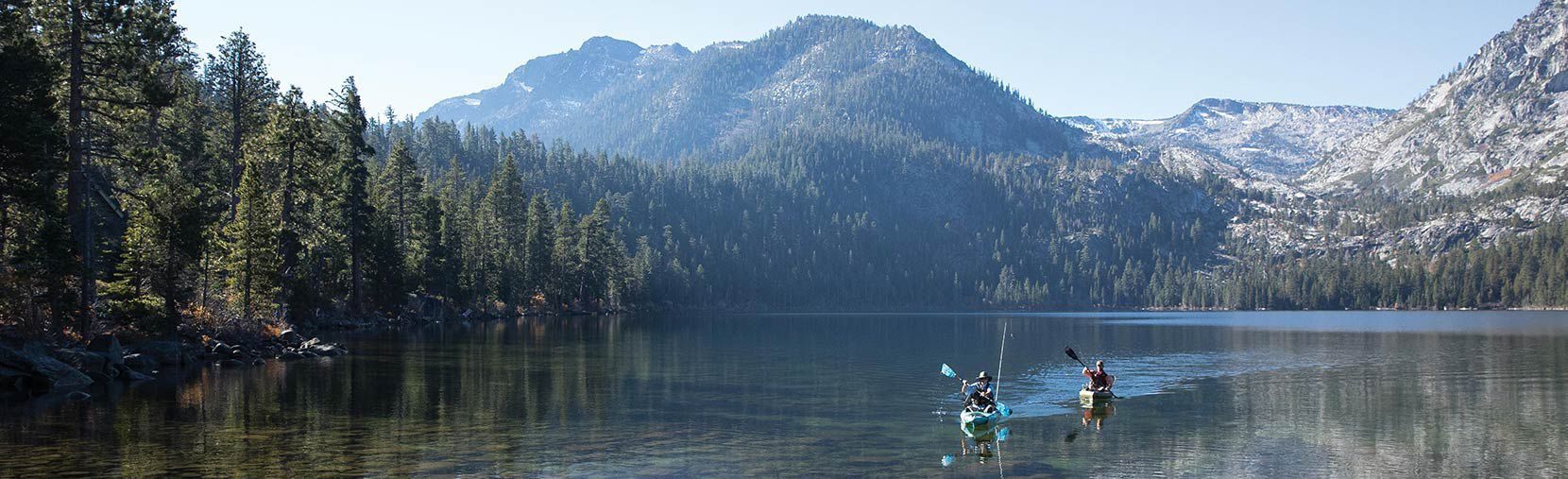Kayakers paddle the discovery angler and F&S Eagle Talon across a clear mountain lake against distant wooded, snow dusted peaks