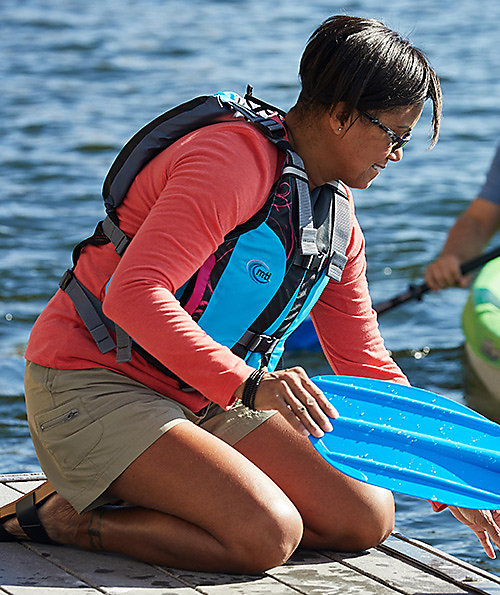 Woman in a colorful long-sleeve Columbia t-shirt, kneeling on a dock getting ready to go kayaking.