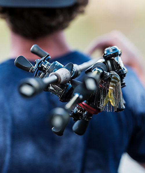 Three baitcasting rod and reel combos with the reels shown in sharp closeup, slung over the right shoulder of a blurred fisherman whose back is to the camera.
