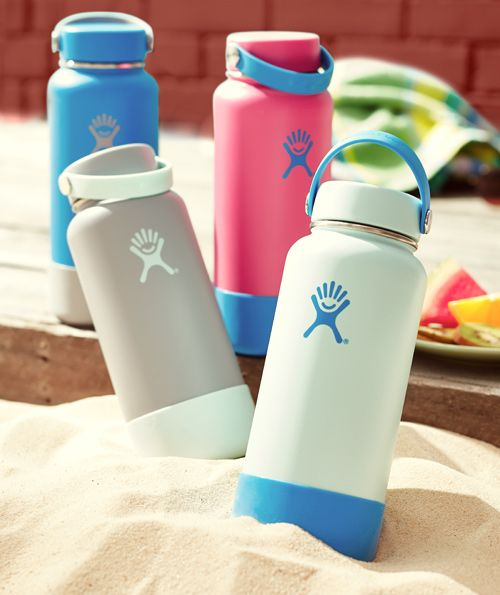 Four Hydro Flask 32 ounce movement bottles of various colors featuring leak proof caps and silicon bumpers sit on a deck and in the sand.