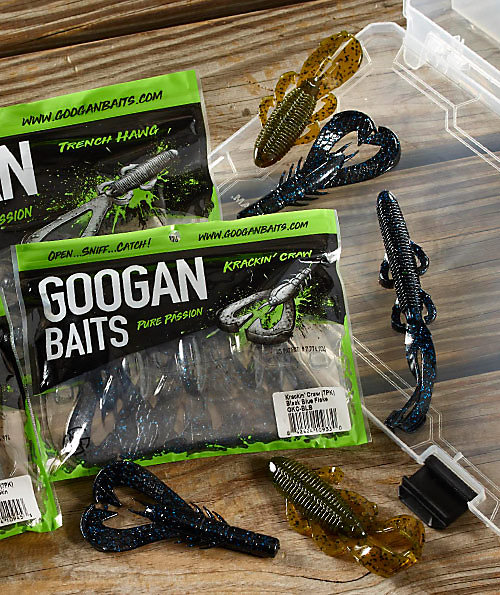 "Closeup shot of ""creature bait"" soft plastics by Googan Baits, shown in and out of the packaging on a bait tray and wooden table."