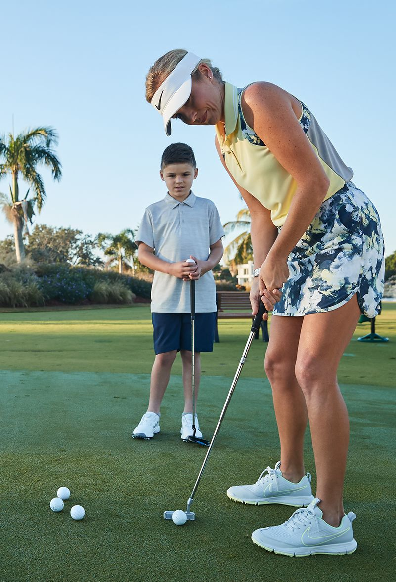 A woman and a boy stand on a golf course. The boy watches as the woman aims a putt, a ball set just by her club head. A group of other balls sits ready nearby.