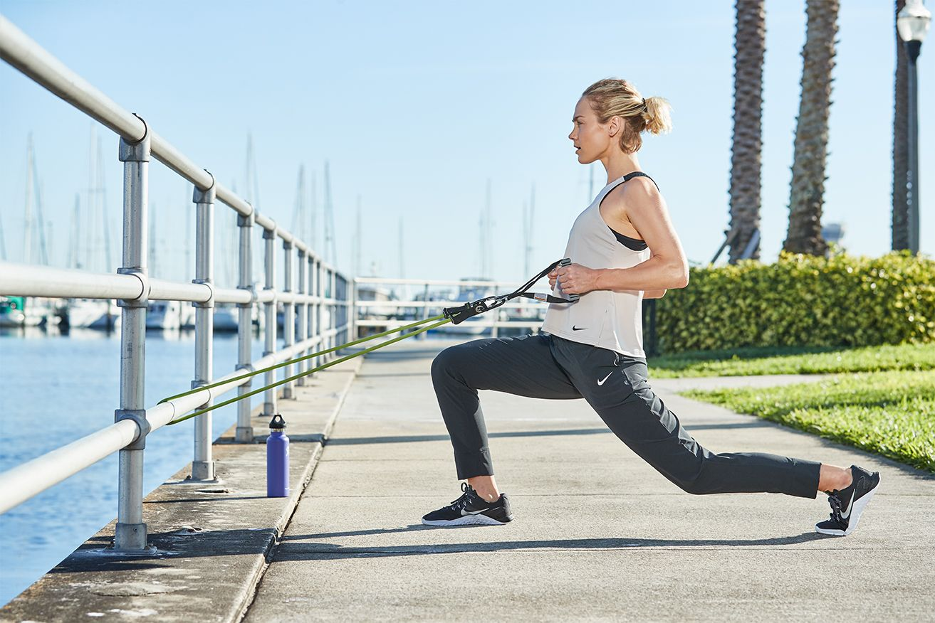 Image of a woman in a raised pier park. She pulls on some excercise stretch bands and lunges while gazing out over the water. Her clothes are marked by the Nike Logo.