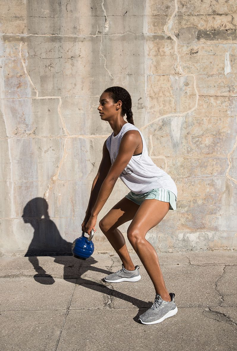 A woman stands on a concrete floor, in front of a concrete wall. She holds a kettle bell and crouches in the midst of an exercise repetition and wears adidas shorts and a shirt.