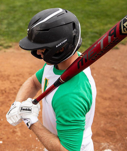 Baseball player gripping a Louisville Slugger Meta Prime BBCOR bat while wearing a Easton Elite X batting helmet with jaw guard in the on-deck circle.