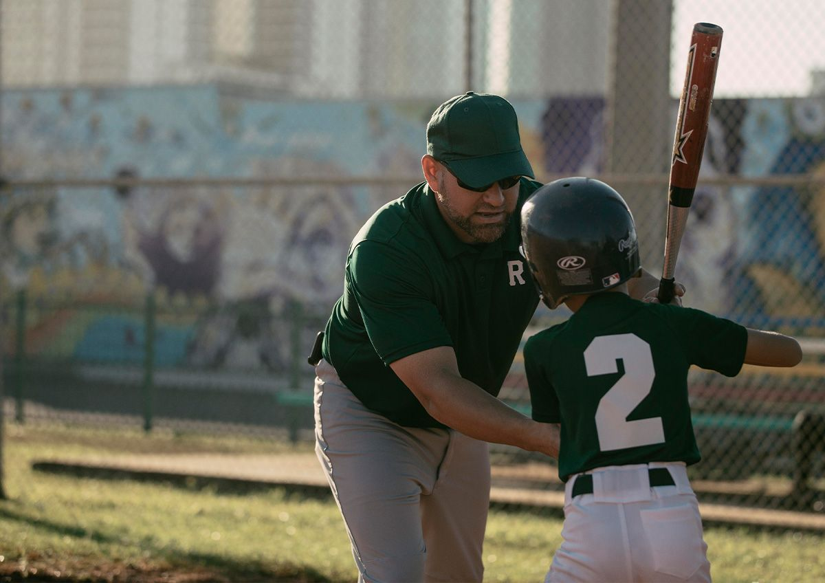Coach helping baseball player